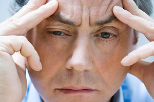 Close-up image of stressed man's face.