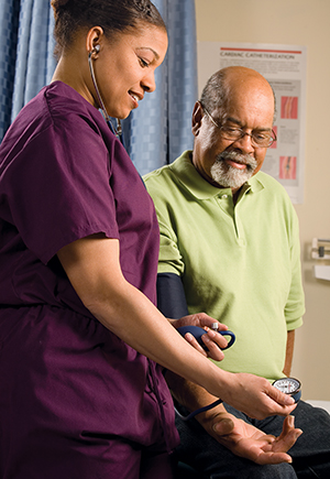 Nurse checking blood pressure of mature male patient.