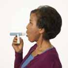 Woman using peak flow meter.