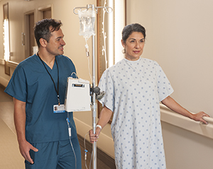 Woman patient walking in hospital hall with an IV pole and nurse.