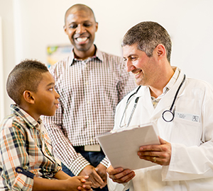 Man and boy talking to doctor.