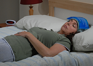 Woman lying in bed with ice pack on forehead.
