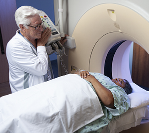 Healthcare provider preparing woman for CT scan.