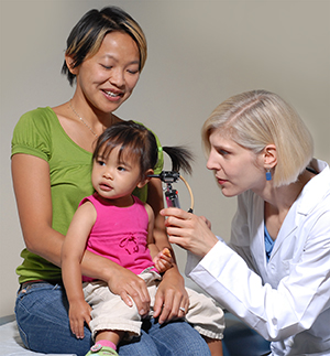 Toddler sitting on woman's lap while doctor examines her ear with otoscope.