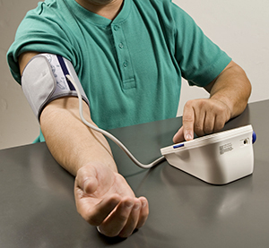 Man taking his blood pressure at home.
