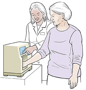 Healthcare provider giving woman bone density test. Woman's hand is in small machine.